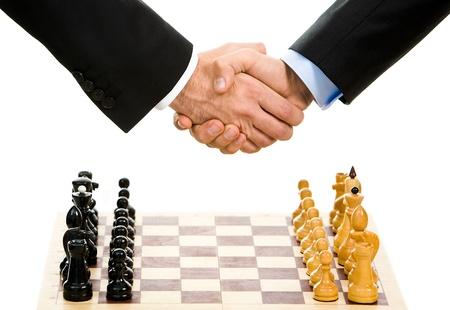 tablero de ajedrez: Imagen de tablero de ajedrez con un apret�n de manos de negocios sobre �l