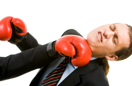 Portrait of defeated businessman in boxing gloves being hit by opponent photo