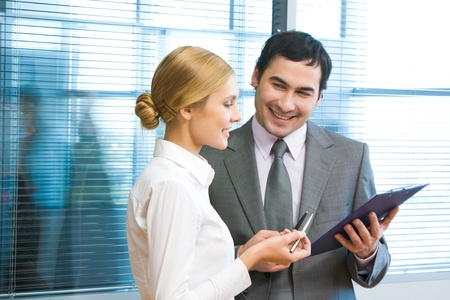 Portrait of executive employees looking at document in male hand and discussing it in office Stock Photo - 9455127