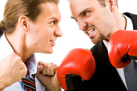 Portrait of aggressive businessmen in boxing gloves looking at each other with angry grin photo