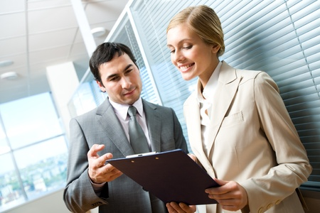 Portrait of executive specialists looking at document in female hand and discussing it in office Stock Photo - 9455123