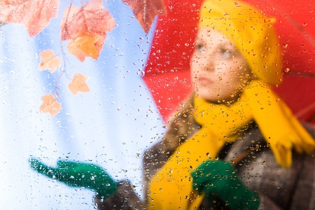 Image of raindrops on window with female under umbrella behind it Stock Photo