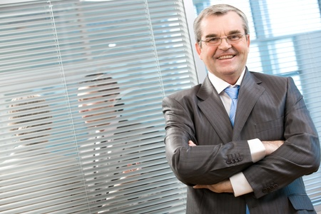 competitive business: Image of senior leader smiling at camera on background of venetian blind