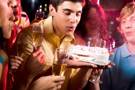 Man with his friends blow out candle on cake at birthday  photo