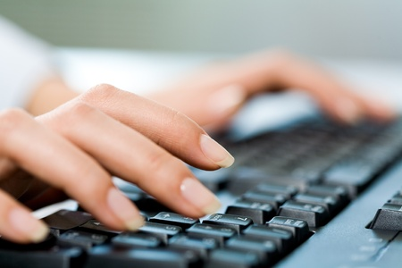 laptop keyboard: Close-up of female hands touching buttons of black keyboard Stock Photo