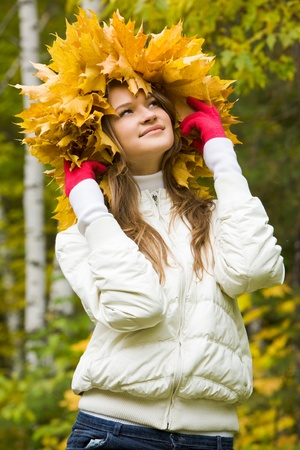 Portrait of smiling young woman wearing wreath of maple leaves   photo