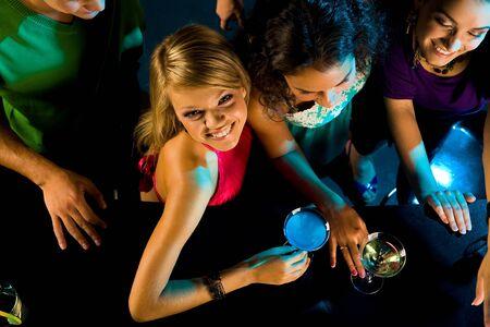 fiesta amigos: Por encima de �ngulo de ni�a feliz mirando la c�mara con sus amigos cerca de por en la barra de