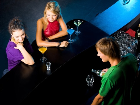 angle bar: Above angle of glamorous girls in the bar with barman near by