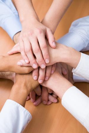 joined hands: Imagen de asociados de negocios de manos en la parte superior de la otra que simboliza el compa�erismo