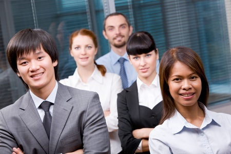 Photo of successful business partners looking at camera with other specialists behind them photo