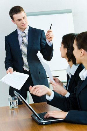 Successful man in suit standing near whiteboard and looking at businesswomen sitting at table and asking him questions photo