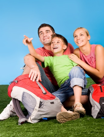 Portrait of family lying on grassland and looking where cute boy pointing during rest photo