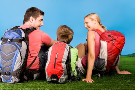 Rear view of family chatting on grassland during rest over blue background  photo