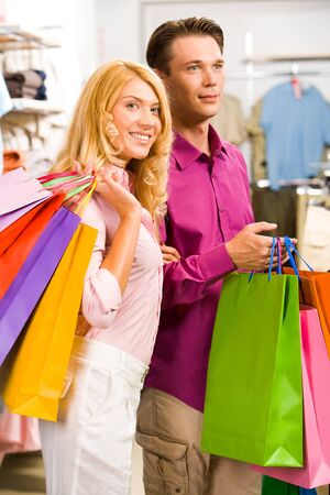 Image of woman holding by man�s hand in the shop  photo