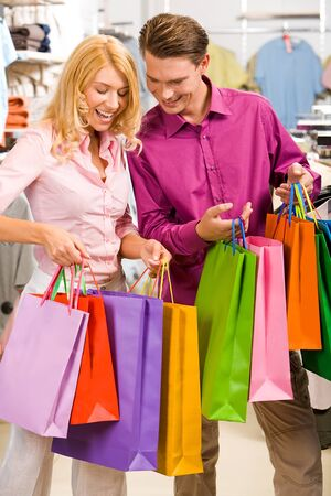 Image of woman showing to man what she bought in the shop  photo