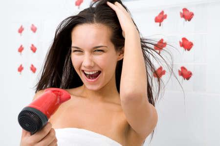 Joyful female drying her hair after washing it photo