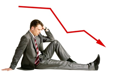 Image of pensive businessman sitting in studio with red arrow showing downward direction photo