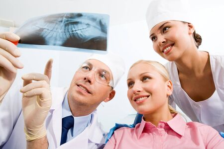 Image of young lady with dentist and nurse showing her x-ray scanned image photo