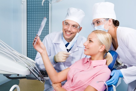 Image of young woman looking at mirror at her teeth surrounded by dentist and assistant photo