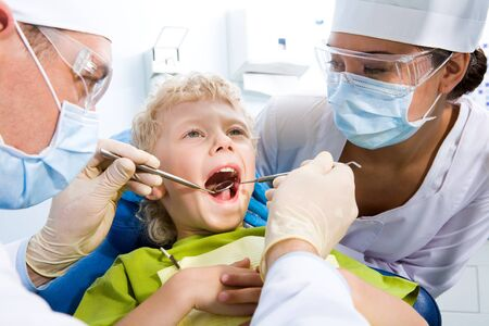 Dental inspection is being given to little boy surrounded by dentist and his assistant Stock Photo - 8523869