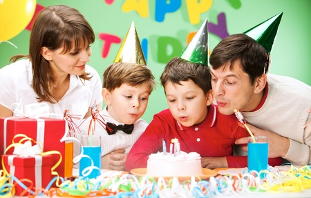 Portrait of family blowing together at the holiday candles on the cake  photo