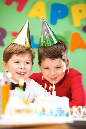 Portrait of happy boys on birthday party with cake near by photo