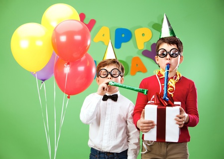 Portrait of smart boys in funny eyeglasses blowing into childish toys photo
