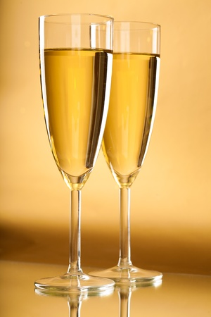 Image of two full champagne flutes over golden background
