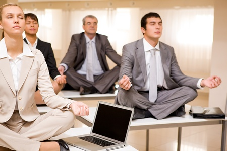 meditating woman: Portrait of meditating business people sitting on desks with their legs crossed in office