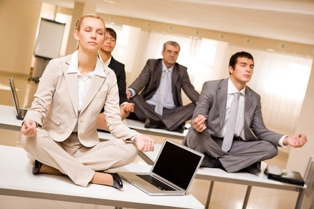 Portrait of meditating partners sitting on desks with their legs crossed in office photo