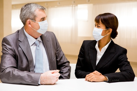 Portrait of two business partners in protective masks looking at each other photo