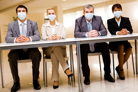 Portrait of group of business partners in protective masks looking at camera photo