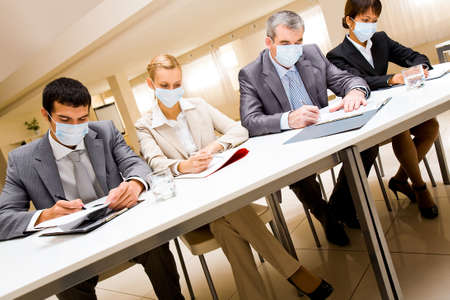 Portrait of group of business partners in protective masks during work photo