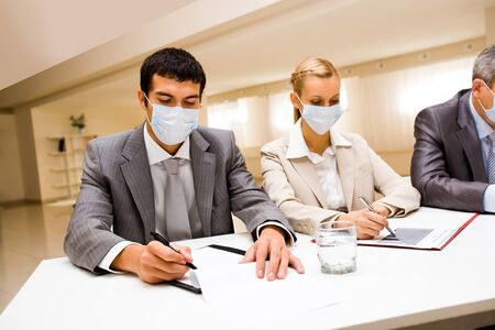 health risk: Portrait of business partners in protective masks making notes
