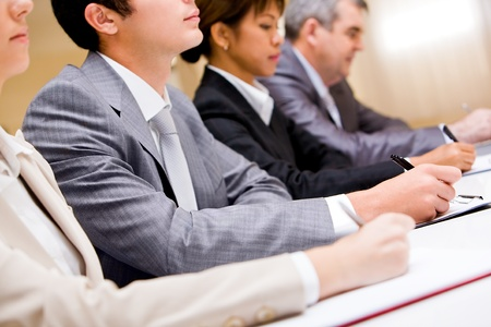 Row of business people making notes during conference photo