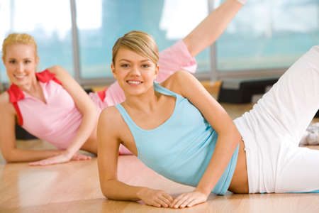 Image of sporty girl doing physical exercise with the other female at background photo
