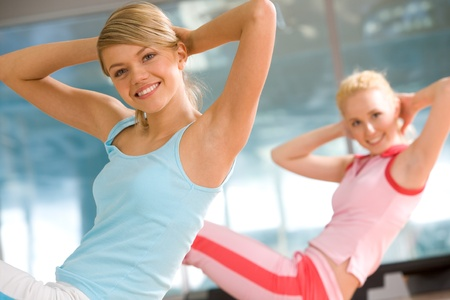 Cheerful girls doing exercise in sport gym with another woman\ at background