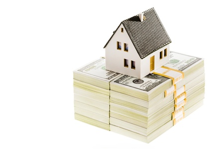 pile dwelling: Close-up of toy house model on top of dollar stack  Stock Photo
