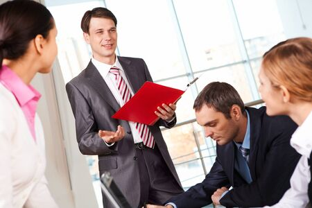 Image of businessman presenting new project or plan to his colleagues photo
