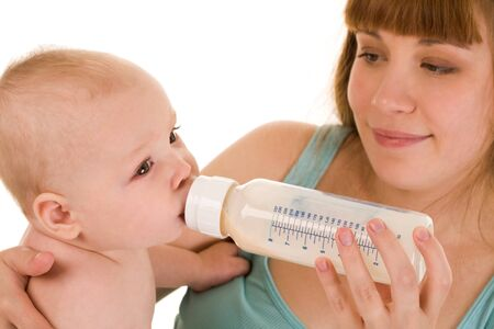 Careful mother holds bottle of milk while her adorable baby drinking it photo
