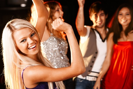 party girl: Portrait of cheerful girl dancing at party with her friends behind