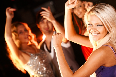 Portrait of cheerful girl dancing at party with her friends behind Stock Photo - 8528342