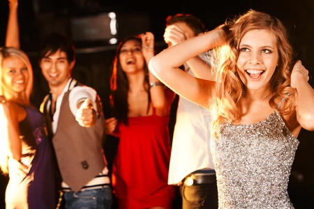 Portrait of joyous girl dancing at party with her friends behind Stock Photo - 8531218