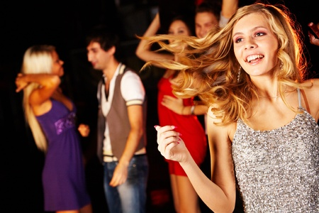 joyous: Portrait of joyous girl dancing at party with her friends behind Stock Photo