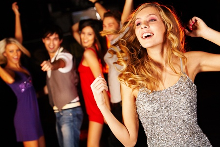 joyous: Portrait of joyous girl dancing at party on background of happy teens