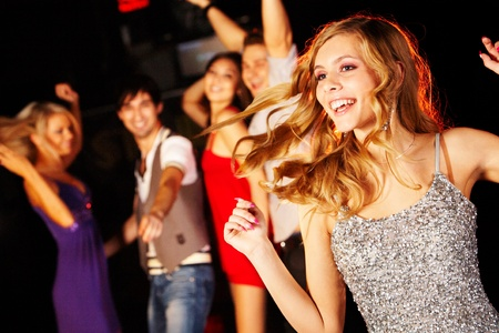 Portrait of joyous girl dancing at party on background of happy teens photo