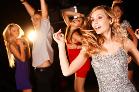 having fun: Portrait of energetic dancer on background of happy teens having fun Stock Photo
