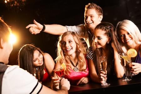 Joyful friends in the bar communicating with barman Stock Photo - 8531215