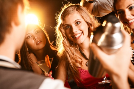 people partying: Pretty girl with cocktail looking at barman at party Stock Photo