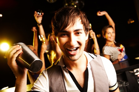 Portrait of smiling male with bottle looking at on background of dancers photo